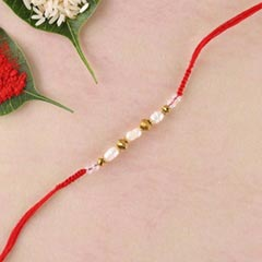 Freshwater pearls,brass beads and crystal in red flat woven rakhi thread - FOR AUSTRALIA