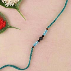 Lava and blue crystal rakhi in teal spiral woven thread